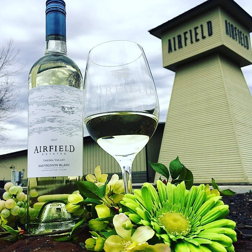 Bottle and glass of wine outside Airfield Estate Winery near Bothell, Washington.