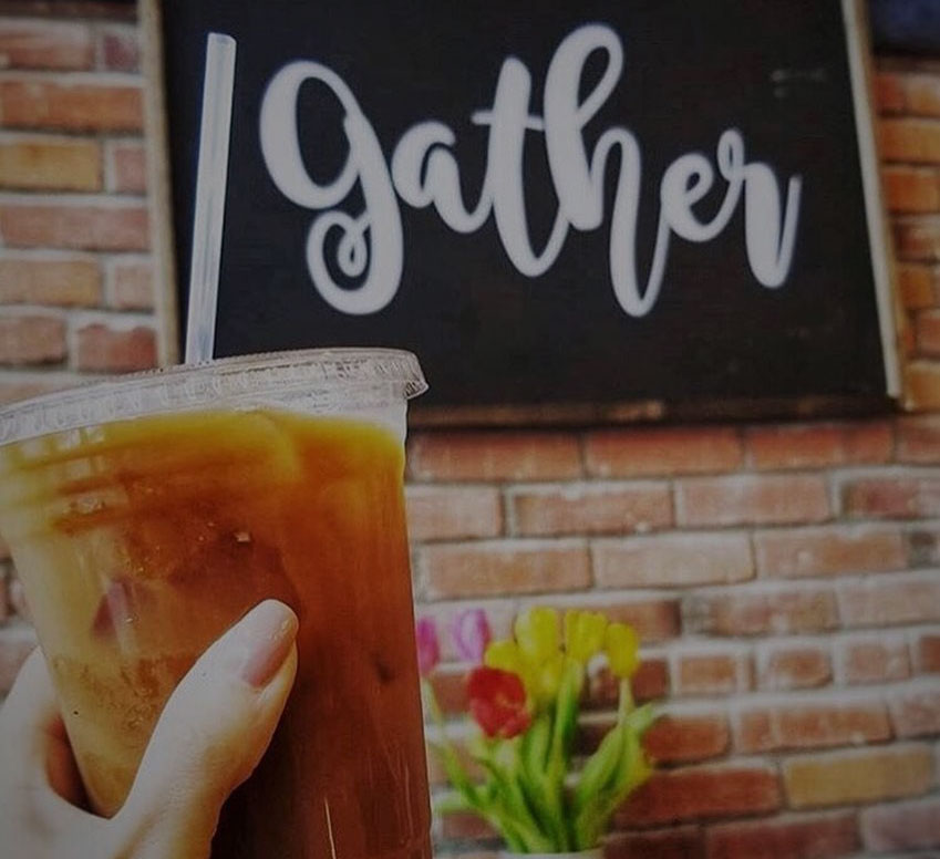 Cup of iced coffee in front of 'gather' sign at Alexa's Café in Bothell, Washington.