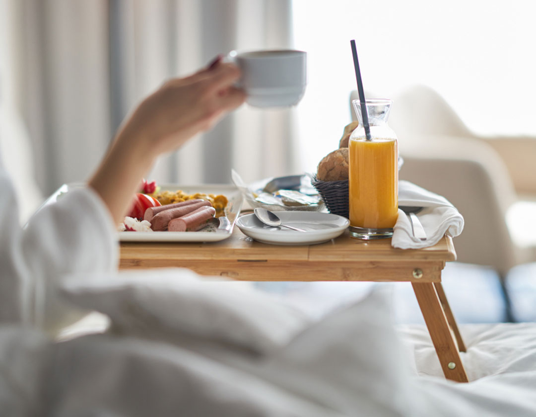 Person eating breakfast in bed at the Bothell Inn & Suites in Bothell, Washington.