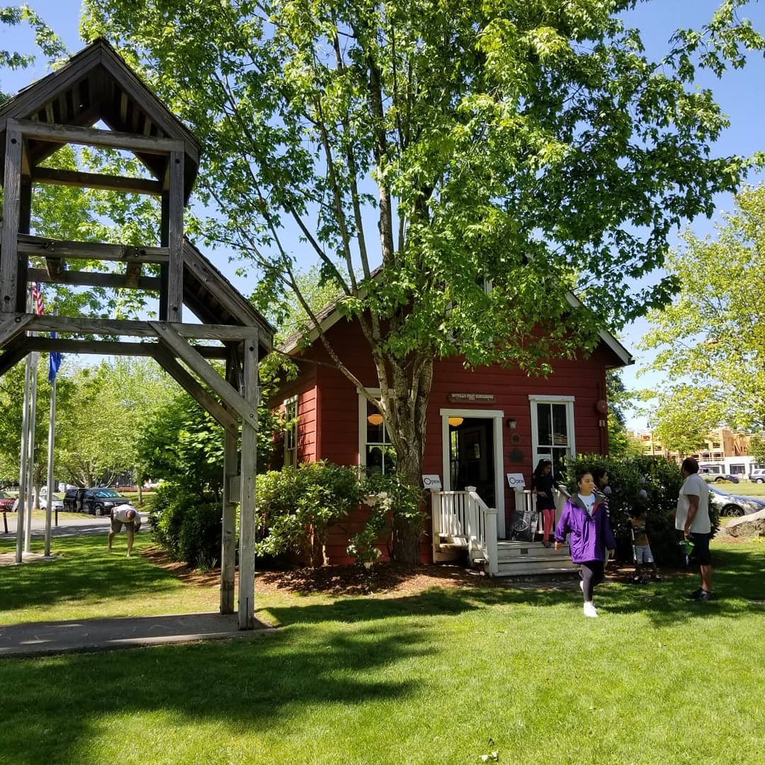 People walking out the front door of Bothell's First Schoolhouse museum.