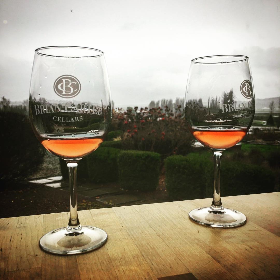 Two glasses of wine infront of the garden at Brian Carter Cellars near Bothell.