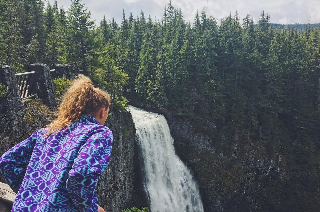 A woman looking over the waterfall at Cherry Creek Falls in Bothell, Washington.