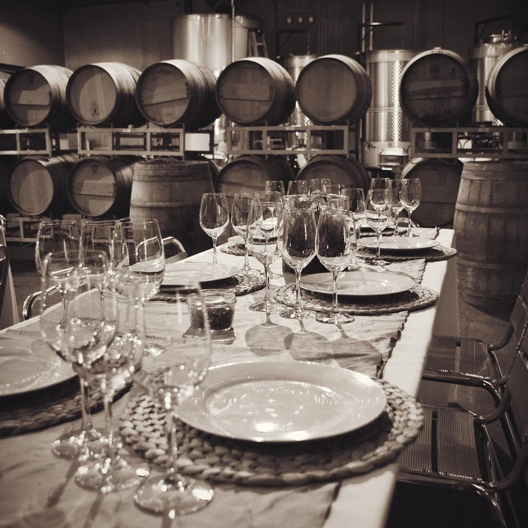 Table with place settings and wine glasses inside of Efeste Winery near Bothell, WA.