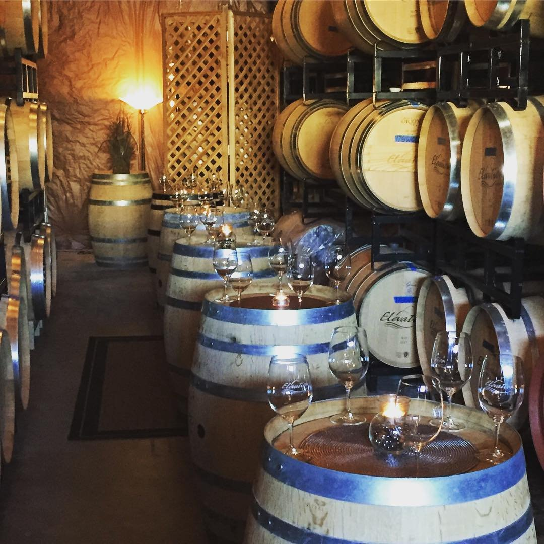 Barrels of wine and wine glasses inside of Elevation Cellars near Bothell, WA.