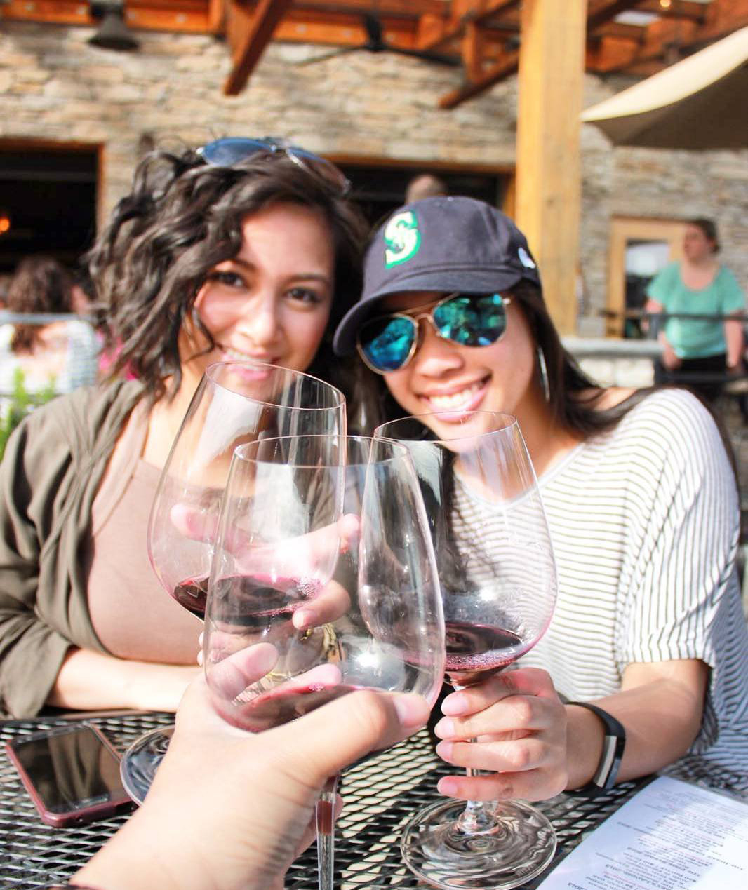 Woman cheersing their wine glasses outside of Gorman Winery near Bothell, WA.
