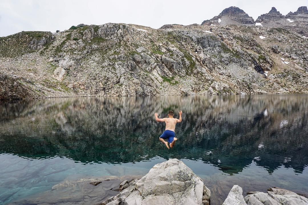 Man jumping into Gothic Basin at Gotchic Lake near Bothell, Washington.