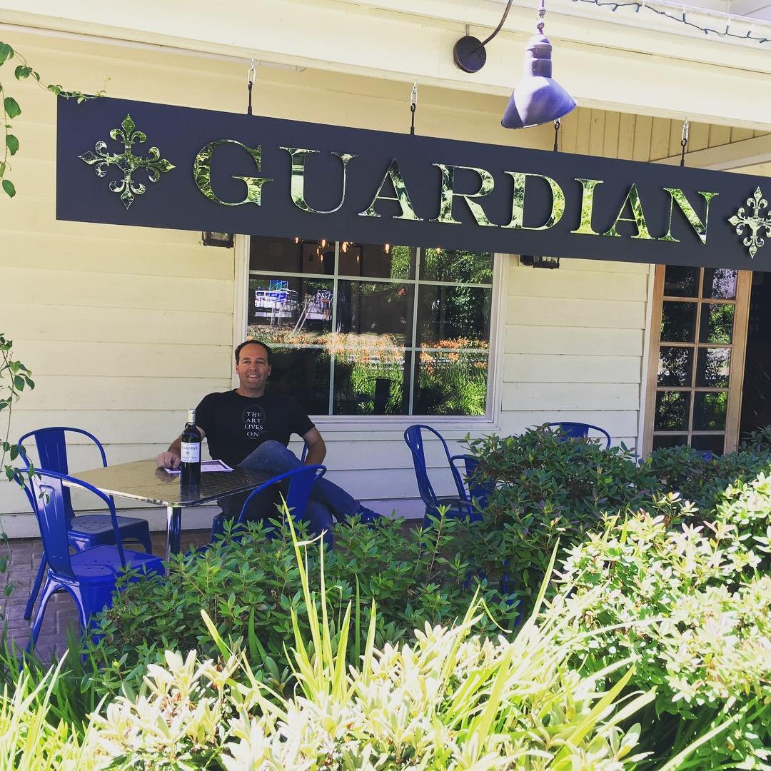 Man sitting on the porch outside of Guardian Cellars near Bothell, Washington.