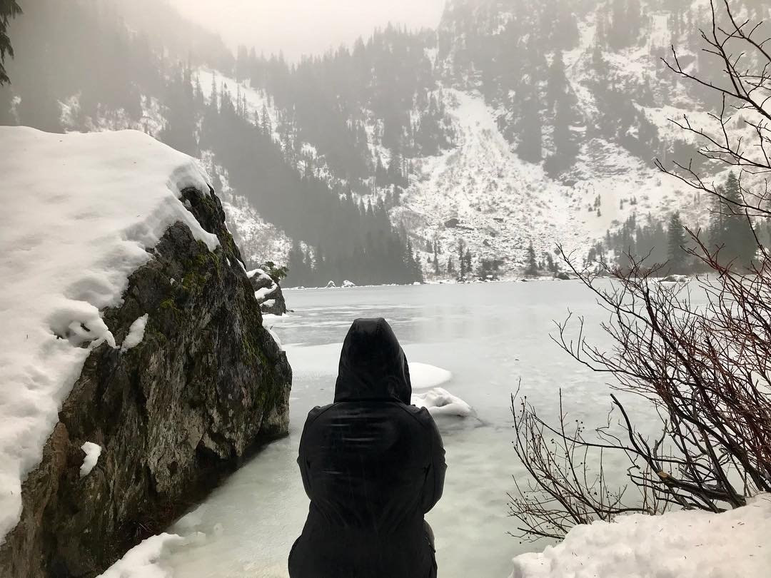 Person looking out on the snowy, frozen Heather Lake near Bothell, Washington.