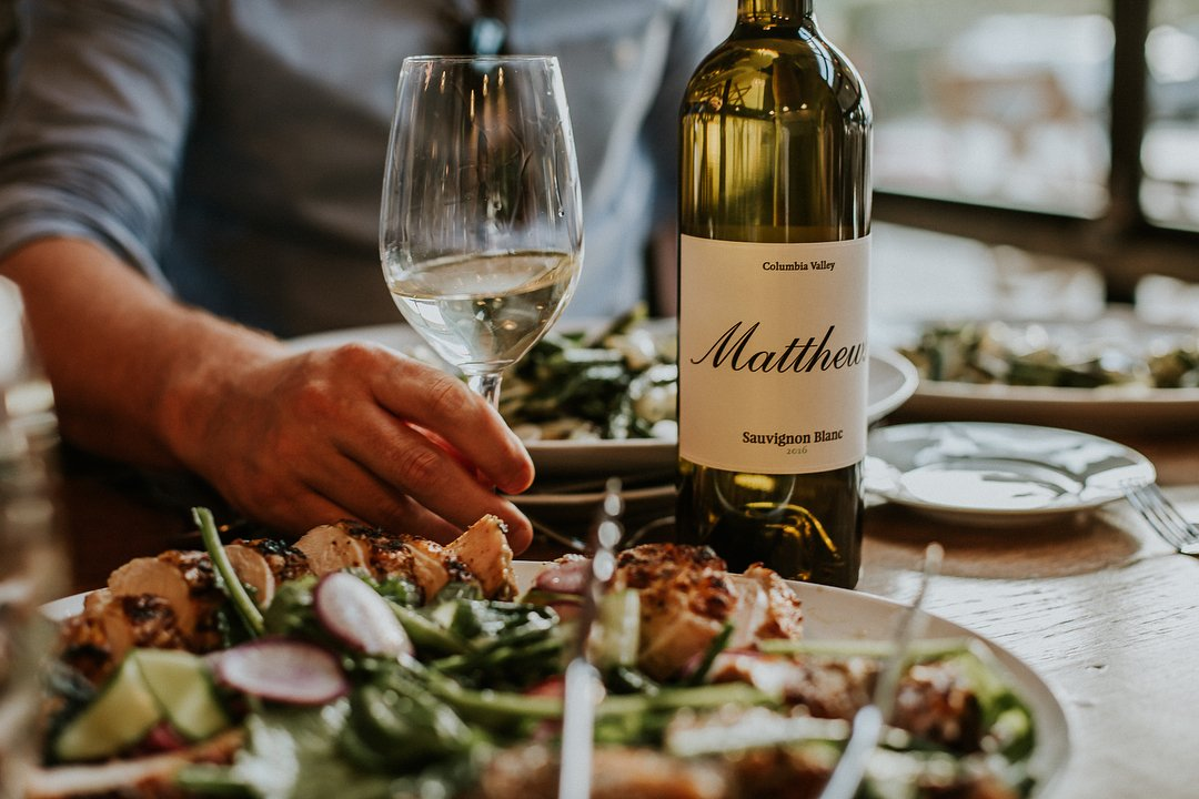 Person with glass of wine, and food, from Matthews Estate Winery near Bothell.