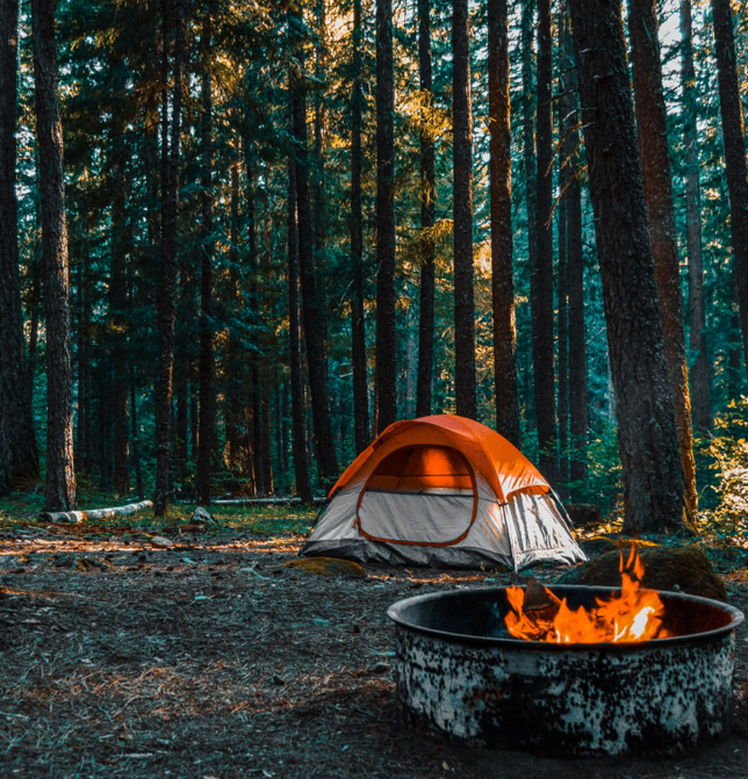Tent pitched in the woods, by a campfire, at Middle Fork Campground in Bothell, WA.