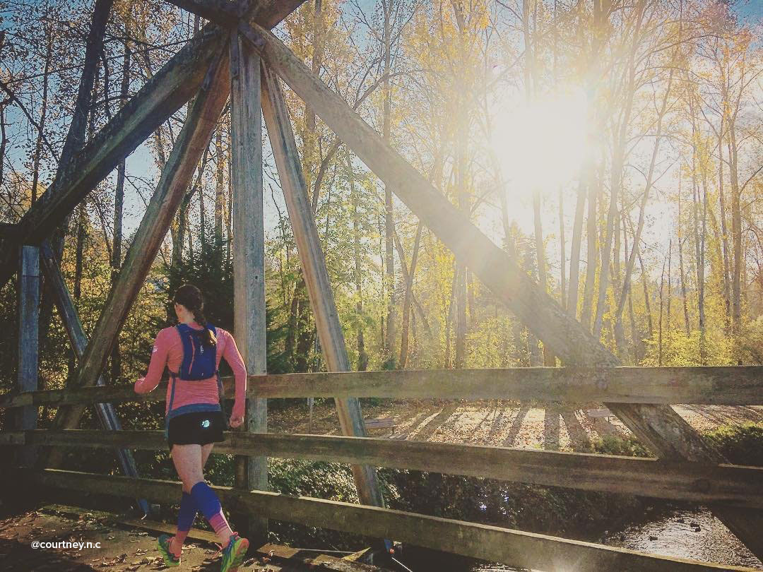 Woman running on bridge over the water at the Park at Bothell Landing in Washington.