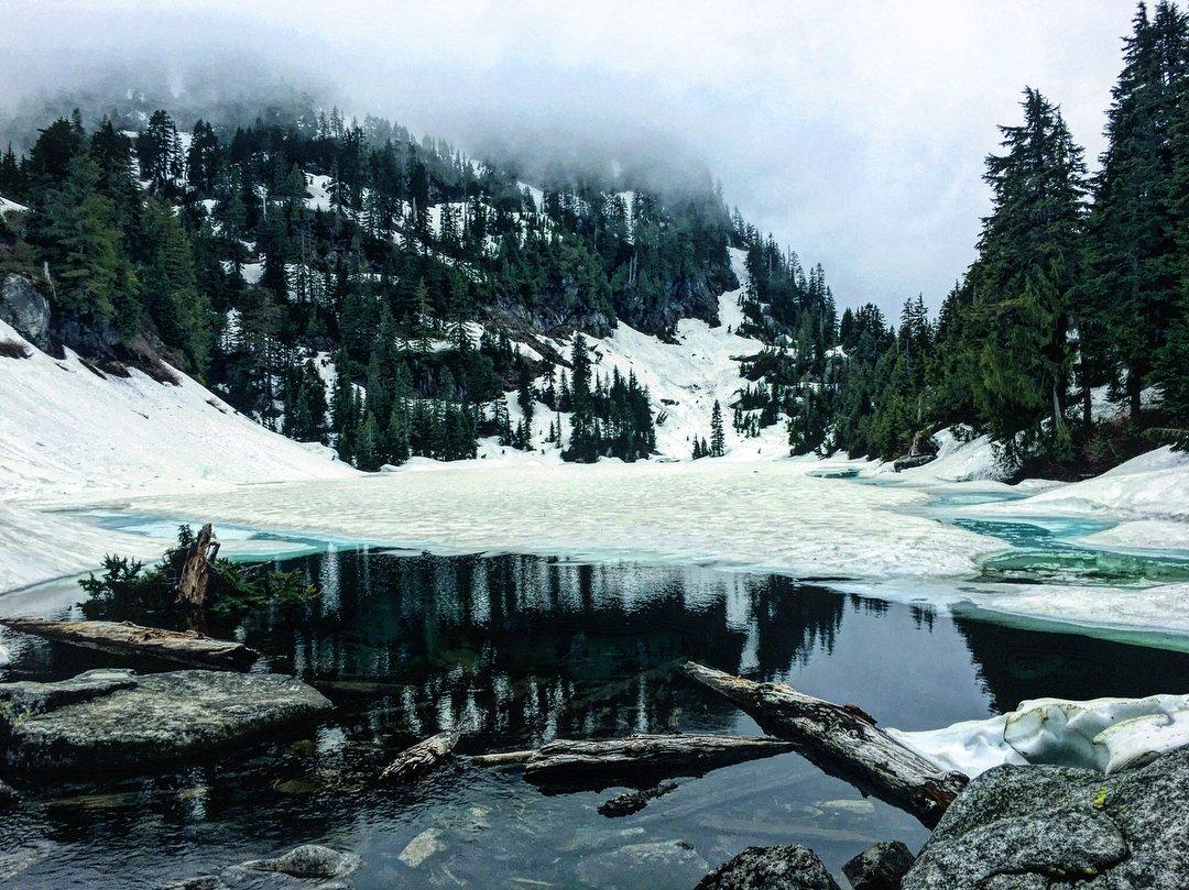 View of the snowy lake and mountains at Pinnacle Lake near Bothell, Washington.