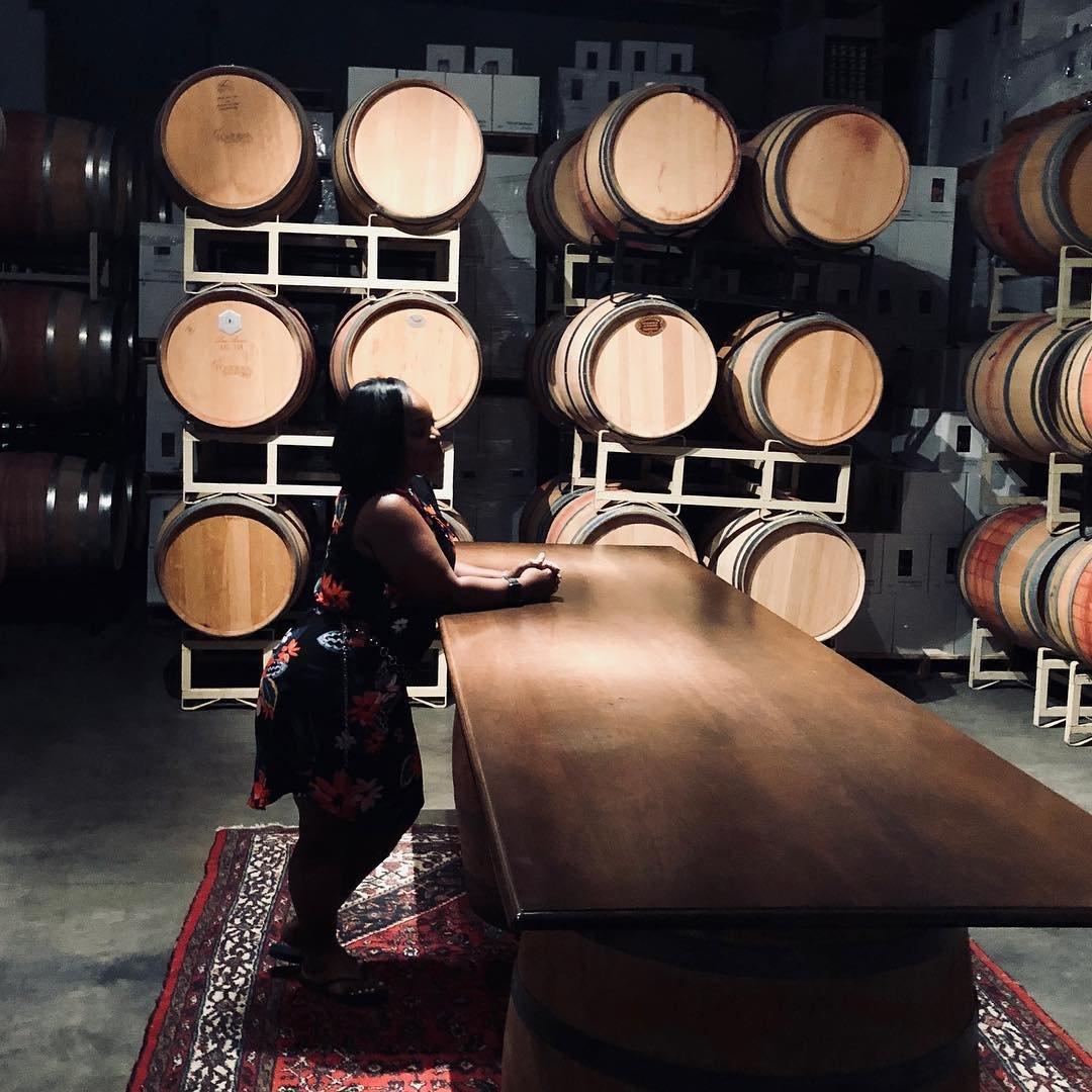 Woman admiring the barrels of wine inside of Pondera Winery near Bothell, WA.