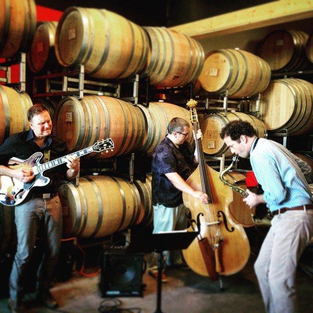 Band playing their instruments among the barrels of wine at Robert Ramsay Cellars.