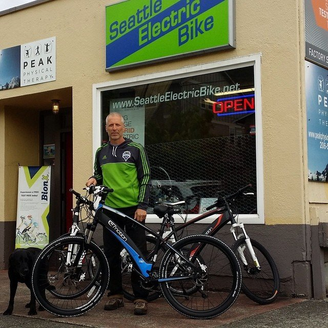 Man standing outside of the Seattle Electric Bike shop with his bike and dog.