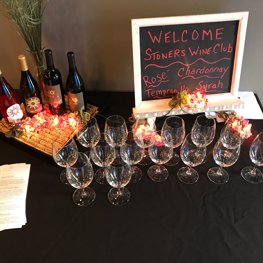 Wine glasses and bottles lined up for the Sol Stone Winery wine club near Bothell.
