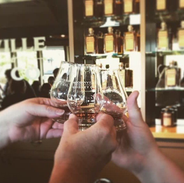People cheersing tasting glasses of whiskey at Woodinville Whiskey Co near Bothell.