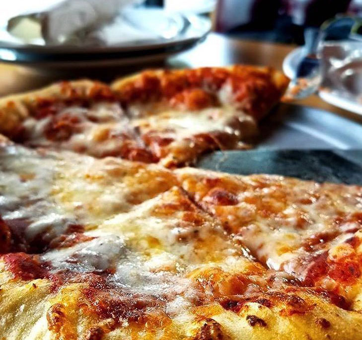 Large cheesy pizza from Zeeks Pizza restaurant in Bothell, Washington.