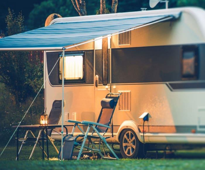 RV at campsite with chairs