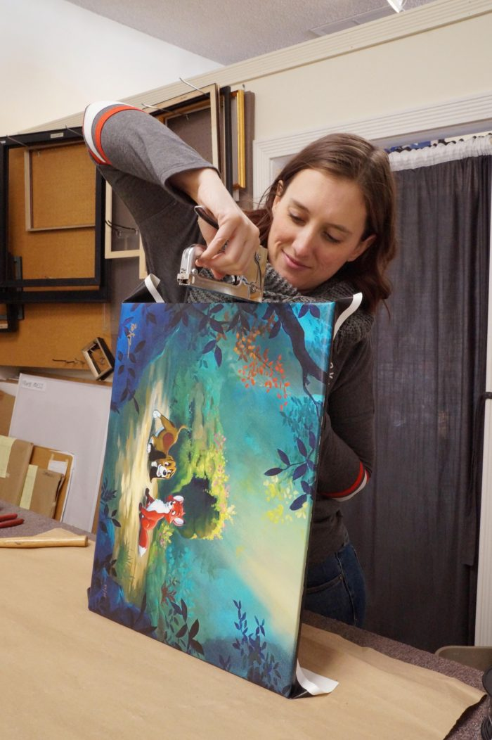 Hannah Waters of Tsuga Fine Arts and Framing framing a painting in the gallerry.