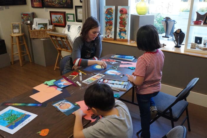 Tsuga Fine Arts & Framing's Hannah Waters teaching children in an art class.