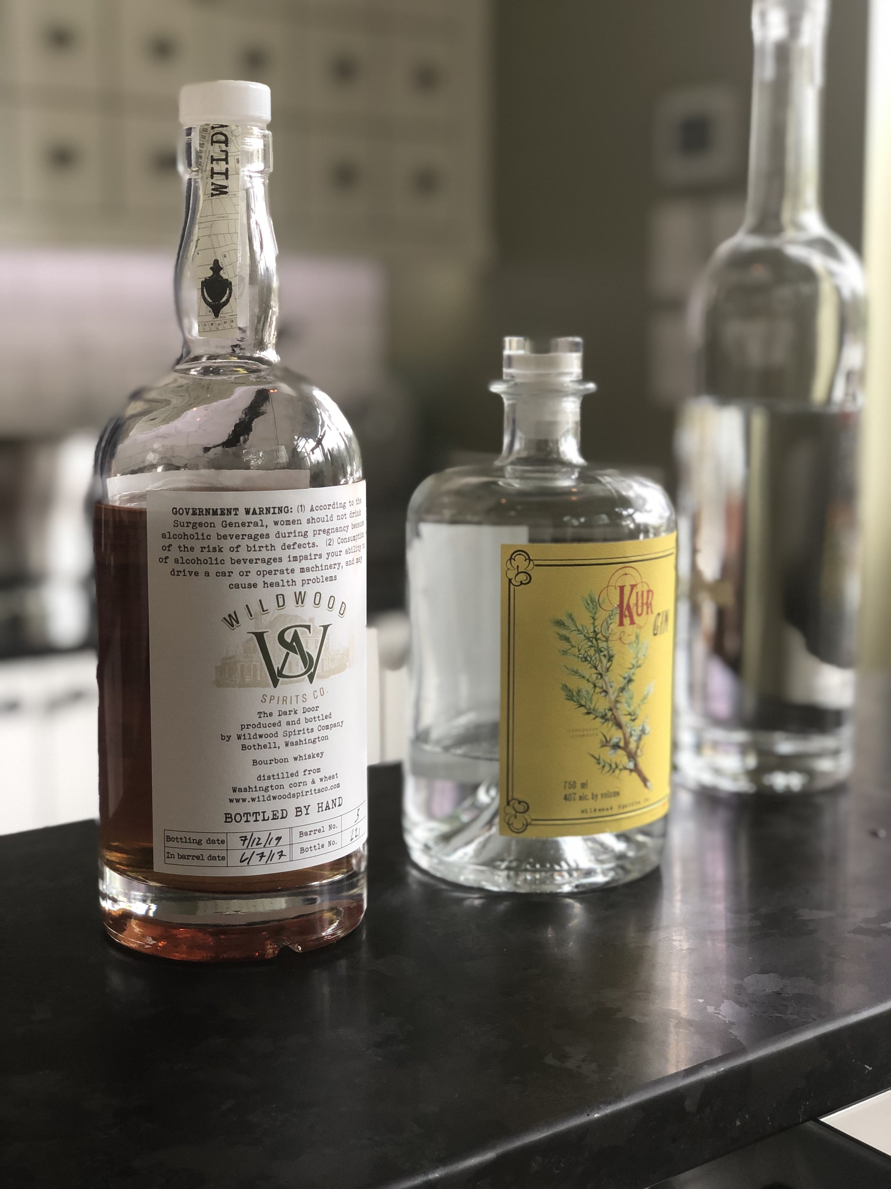 Wildwood Spirits Co apothecary style tasting room, bourbon and gin on counter.